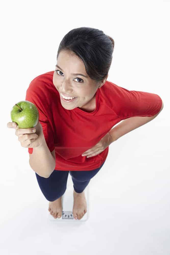 Das Mädchen hat Gewicht und hält einen Apfel in der Hand.