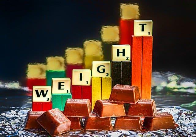 tabliczki czekolady i słupki pokazujące wzrost wagi