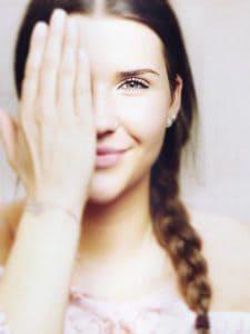 das Mädchen, das das Auge bedeckt, die Sehkraft