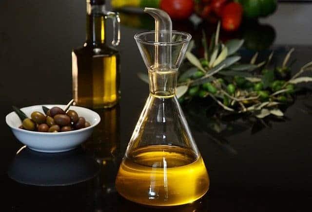 Flakon aus Öl und grünen Oliven