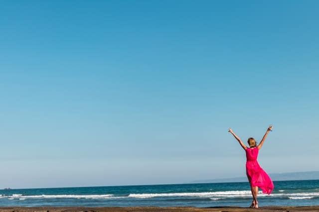 eine Frau in einem roten Kleid, die an der Küste steht