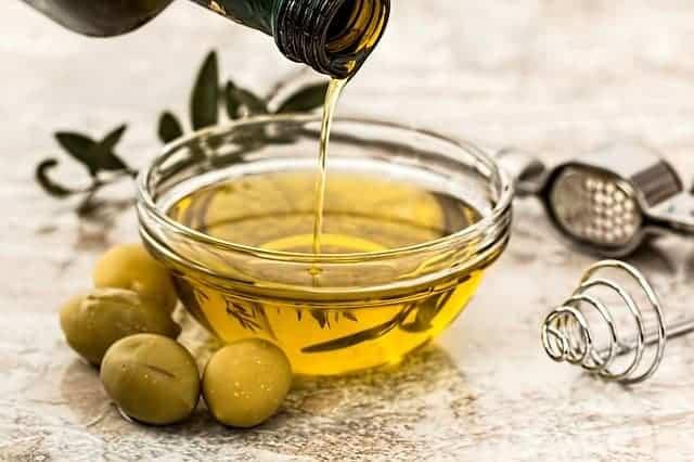 Öl in eine Schüssel gegossen, daneben grüne Oliven