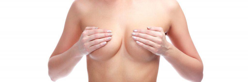 die Frau bedeckt ihre Brüste mit den Händen