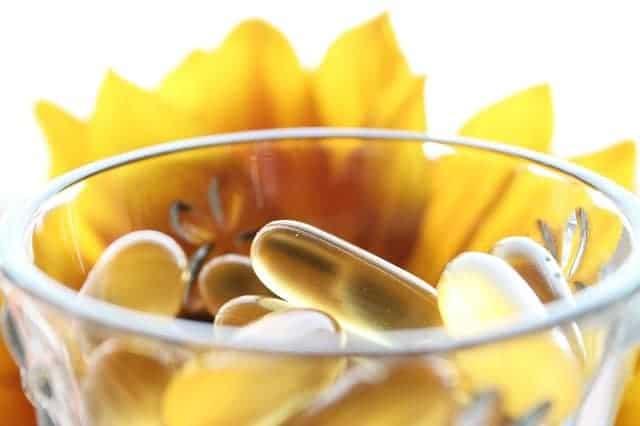 tTabletten in einem Glas, gelbe Blume im Hintergrund