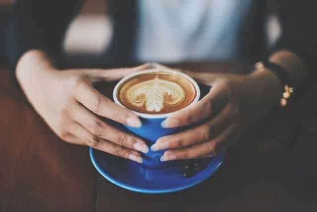 Tasse Kaffee in den Händen halten