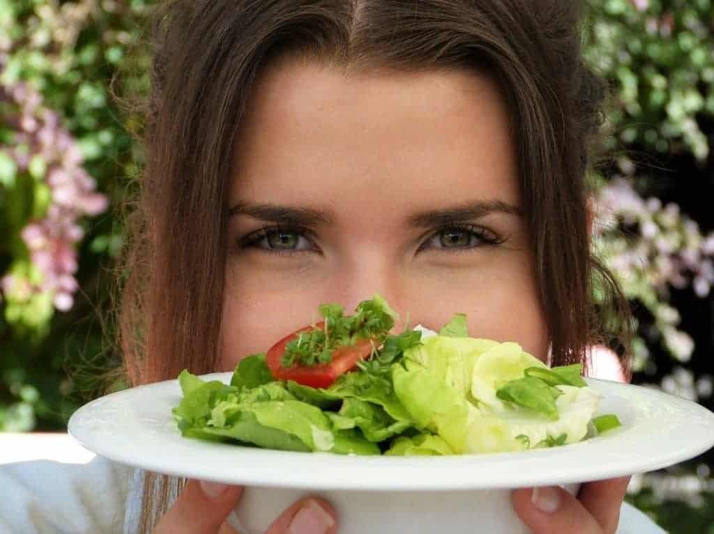 die Frau hält einen Teller mit Salat