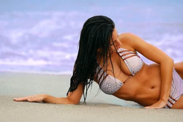 die Frau im Badeanzug liegt am Strand
