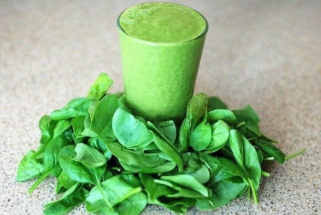 Ein Glas mit einem grünen Smoothie, rundherum Spinatblätter