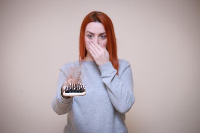 eine Frau schaut auf eine Haarbürste voller Haare