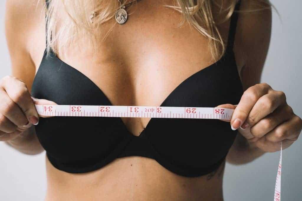 Frau misst ihre Brüste mit einem Zentimeter