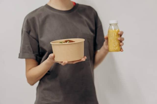Frau hält eine Schüssel mit Essen und einen Shake