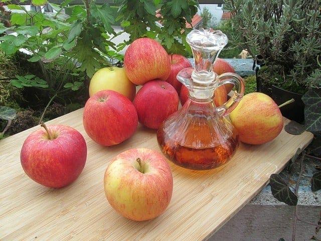 Frische Äpfel und eine Flasche Apfelessig auf dem Tisch