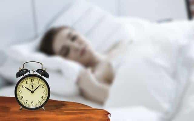 eine Frau schläft mit einem Wecker neben ihrem Bett