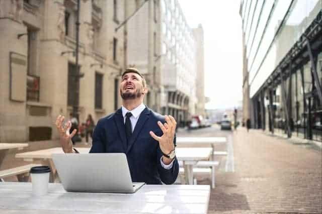 Ein nervöser Mann arbeitet an seinem Laptop