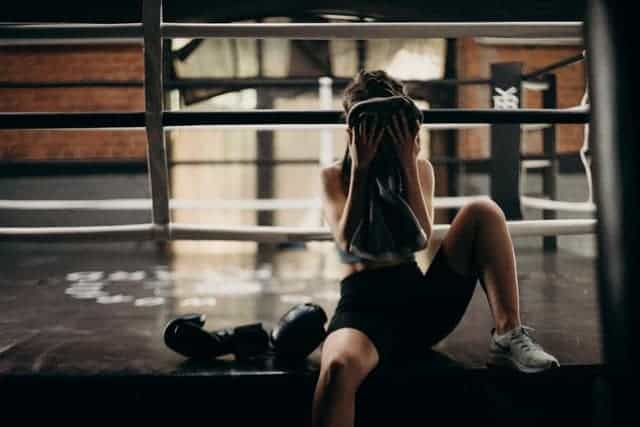 Frau wischt sich nach anstrengendem Workout den Schweiß aus dem Gesicht
