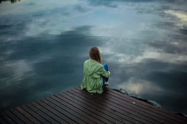 eine Frau sitzt auf der Kante eines Stegs und schaut ins Wasser