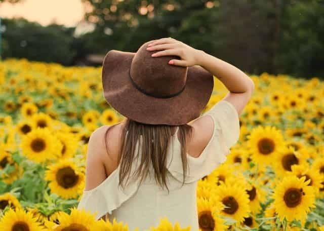 eine Frau geht durch ein Feld mit Sonnenblumen