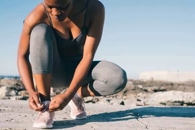 Frau in Sportkleidung bindet ihren Schuh