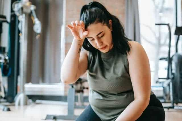 Übergewichtige Frau müde nach einem Training