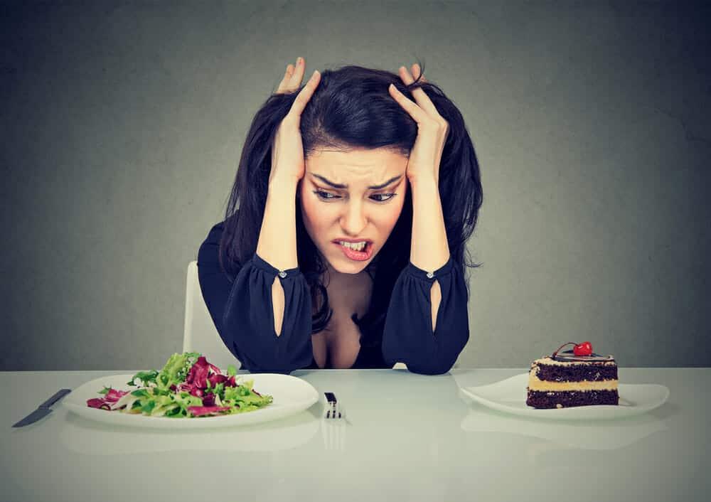 eine Frau sitzt an einem Tisch mit einem Teller Kuchen und einem Teller Salat