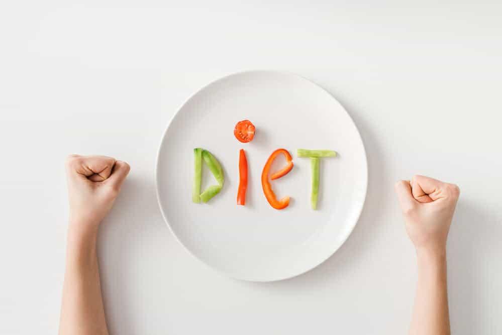Geballte Fäuste, ein Teller, ein paar Gemüsestücke auf dem Teller