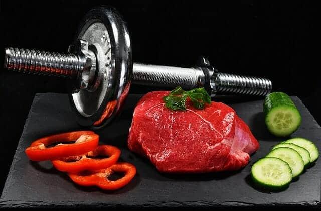 Hanteln, ein Stück Fleisch und Gemüse