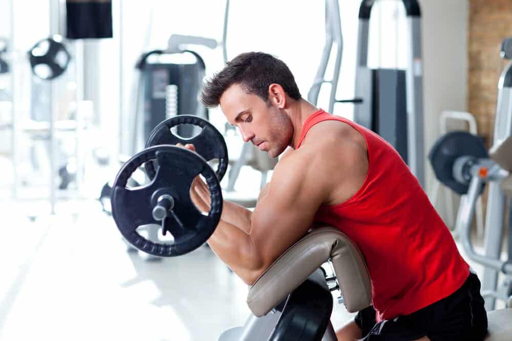 Ein Mann trainiert mit einer Langhantel im Fitnessstudio.