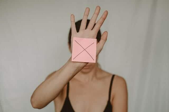 eine traurige Frau hält einen Pappkarton mit einem X vor sich